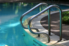 Swimming pool handrail. Stainless steel handrails by the swimming pool are shining with a strong feeling Royalty Free Stock Image