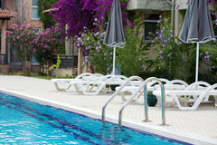 Swimming pool with handrail and sunbeds. A handrail of your private swimming pool with sunbeds Stock Image