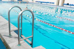 Swimming pool handrails. Clear blue water on background stock photo