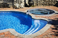 Swimming pool with hot tub. Outdoor inground residential swimming pool in backyard with hot tub Royalty Free Stock Image