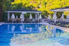 Swimming pool at hotel with bar. Empty hotel, palm trees, umbrellas.  royalty free stock photos