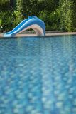 Swimming pool in a hotel with a dolphin slider on the pool side. Swimming pool in a hotel with a dolphin slider on the pool side with clear and clean blue good stock photos