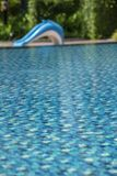 Swimming pool in a hotel with a dolphin slider on the pool side. Swimming pool in a hotel with a dolphin slider on the pool side with clear and clean blue good stock photo