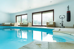 Swimming pool inside expensive house. View of swimming pool inside expensive house Royalty Free Stock Images