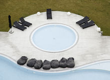 Swimming pool with Jacuzzi. Upper level detail in a swimming pool with sun loungers, summer Stock Photography