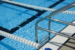 Swimming pool ladder. Stairs set to climb in or out of the pool. Racing lanes can be seen at the bottom of the pool. Exercise by swimming to relieve joint pain royalty free stock images