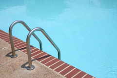 Swimming Pool Ladder. Aluminum ladder leads to a clear blue swimming pool Stock Image