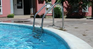 Swimming Pool Ladder. Outdoor Swimming Pool Ladder. Sunlight Reflections In Swimming Pool Water. Close Up View - DCi 4K Video stock footage