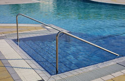 Swimming pool with ladder and the steel handrail in an exclusive. Luxurious resort royalty free stock image