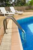 Swimming pool ladder and sunloungers Royalty Free Stock Images