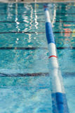 Swimming Pool Lane Marker. Picture of a lane line in a outdoor swimming pool. Focus centered on the red stripe on the lane line Royalty Free Stock Image