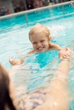 Swimming pool lesson. Vertical shot of a toddler learning how to swim in a swimming pool Royalty Free Stock Photos