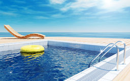 Swimming pool with life ring, beach lounger, sun deck on sea view for summer vacation. Blue swimming pool with yellow life ring floating on water surface, beach Royalty Free Stock Photo