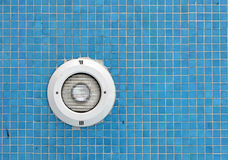 Swimming pool light. A circular shaped swimming pool light within blue porcelain tiles Royalty Free Stock Photos