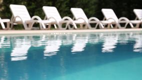 Swimming pool with lounge chairs stock video