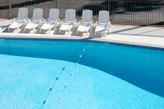Swimming pool and lounge chairs. Empty swimming pool with lounge chairs on deck Royalty Free Stock Photos
