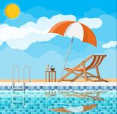 Swimming pool and lounger. Swimming pool and ladder. Umbrella, wooden lounger. Table with coconut and cocktail. Sky, clouds, sun. Vacation and holiday concept Stock Photo