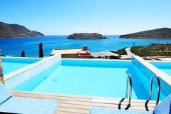Swimming pool at luxury hotel with a view on Spinalonga Island Stock Photos