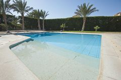 Swimming pool at a luxury tropical holiday villa. Luxury villa show home at tropical summer holiday resort with swimming pool in garden Stock Images