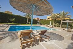 Swimming pool at a luxury tropical holiday villa. Luxury villa show home at tropical summer holiday resort with swimming pool and sun chairs in garden Royalty Free Stock Image