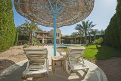 Swimming pool at a luxury tropical holiday villa. Luxury villa show home at tropical summer holiday resort with swimming pool and sun chairs in garden Royalty Free Stock Photos