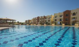 Swimming pool in a luxury tropical hotel resort. Large swimming pool with buildings at a luxury tropical hotel resort Royalty Free Stock Image