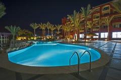 Swimming pool in luxury tropical hotel resort at night. View over a swimming pool in luxury tropical hotel resort at night with date palm trees Royalty Free Stock Image