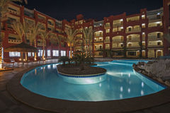 Swimming pool in luxury tropical hotel resort at night. View over a swimming pool in luxury tropical hotel resort at night with date palm trees Royalty Free Stock Images