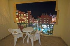 Swimming pool in luxury tropical hotel resort at night. View over a swimming pool in luxury tropical hotel resort at night with date palm trees Stock Photo