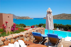 Swimming pool by luxury villa. With a view on Spinalonga Island, Crete, Greece royalty free stock image