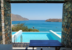Swimming pool by luxury villa. With a view on Spinalonga Island, Crete, Greece royalty free stock photos