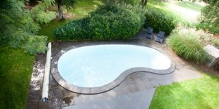 The swimming pool at luxury villa. Empty swimming pool bean at luxury villa royalty free stock image