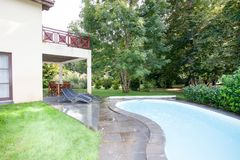 The swimming pool at luxury villa. Luxurious swimming pool in backyard of a residential home luxury villa stock image
