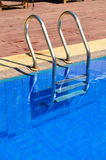 Swimming pool with metal ladder Royalty Free Stock Photos