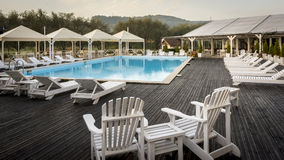 Swimming pool in the morning. With white chairs Stock Photography