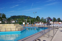 Swimming pool at mountain resort. Mountain resort: swimming pool and chaise lounges Royalty Free Stock Photography
