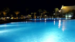 Swimming Pool at Night. Beach Loungers are Near a Large Swimming Pool. Tall Palms Are Planted All Over the Territory. Territory is Shining with the Lights at stock footage
