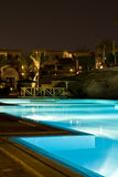 Swimming pool night scene. Scenic view of illuminated swimming pool in tourist hotel complex viewed at night, Sharm el Sheikh, Egypt Royalty Free Stock Images