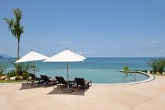 Swimming pool by ocean. Sun loungers and swimming pool beside ocean, Puerta Vallarta resort, Mexico stock photos