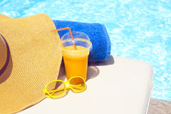 Swimming pool, orange juice, beach towel, sunglasses Royalty Free Stock Photography