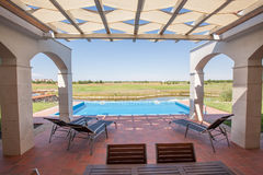 Swimming pool outside luxury home Royalty Free Stock Image