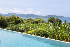 Swimming pool overlooking view andaman sea mountains and blue sk Royalty Free Stock Image