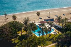 Swimming pool with palm trees by the sea beach. Aerial view Stock Image