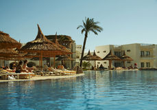 Swimming-pool and parasols group. Clear pool and parasols group in hotel stock images