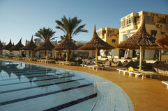 Swimming-pool and parasols group on resort. Clear pool and parasols group in hotel royalty free stock image
