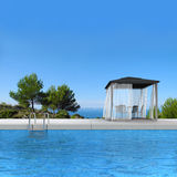 Swimming pool with pavilion. Fictitious 3D rendering showing a swimming pool with pavilion and fantsatic view to the sea Stock Images