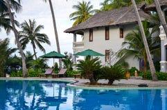 Swimming pool in Phan Thiet, Vietnam. Phan Thiet, Vietnam - Mar 26, 2017. Swimming pool of resrort with palm trees in Phan Thiet, Vietnam. Phan Thiet belongs to Stock Photo