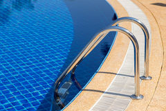 Swimming pool with pool ladder in hotel Royalty Free Stock Image