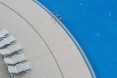 Swimming pool and recliners Royalty Free Stock Image
