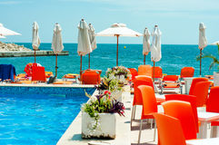 Swimming pool with red sun beds and umbrellas against an ocean Stock Photo